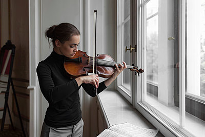 Confident woman with sheet music on window sill playing violin in mansion - p1166m2011255 by Cavan Images