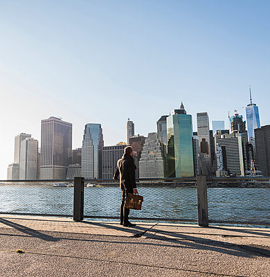 USA, Brooklyn, back view of businessman with briefcase standing in front of Manhattan skyline - p300m1206300 by Uwe Umstätter