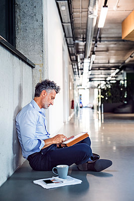 Mature businessman sitting on the floor using tablet - p300m1568085 von HalfPoint