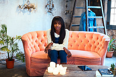 Portrait of young woman sitting on the couch in her loft - p300m1581601 by Bonninstudio