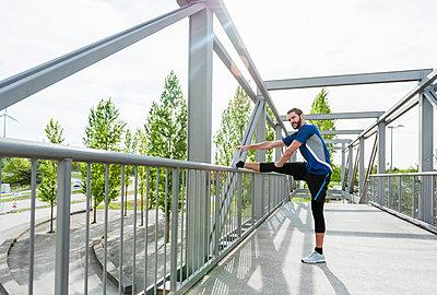 Man stetching on a bridge - p300m1587115 by Daniel Ingold