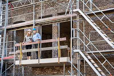 Professional team examining construction site while standing in balcony - p300m2256461 by Peter Scholl