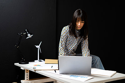 Businesswoman using laptop while sitting on desk by black wall at office - p300m2274709 by Giorgio Fochesato