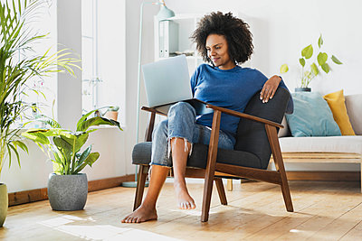 Smiling woman using laptop while sitting on armchair at home - p300m2277512 by Steve Brookland