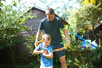 Boy and father playing with plastic hoop in garden - p429m1494554 by Peter Muller