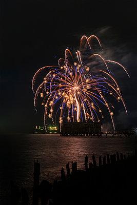 Fireworks brighten the nighttime sky; Astoria, Oregon, United States of America - p442m1180105 by Robert L. Potts