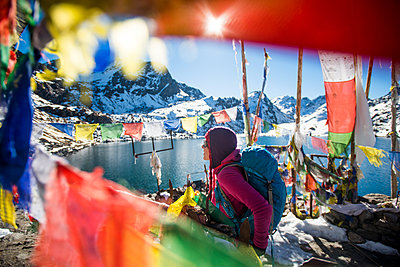 A trekker stands among prayer flags beside the holy lakes at Gosainkund in the Langtang region, Himalayas, Nepal, Asia - p871m1196978 by Alex Treadway