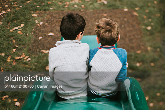Rear view of two brothers sitting on slide at playground - p1166m2130780 by Cavan Images