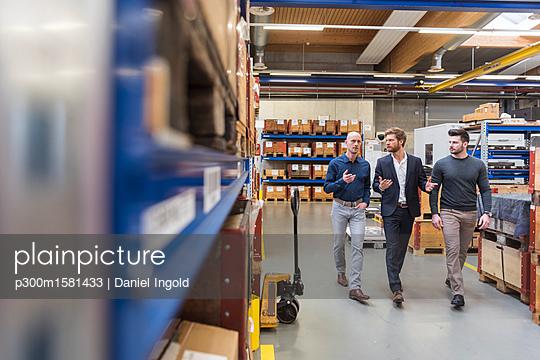 Three men walking and talking in factory storeroom - p300m1581433 von Daniel Ingold