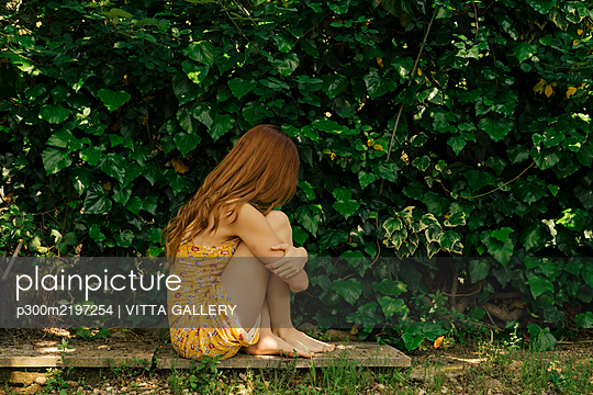 Sad young woman hugging knees while sitting by plants at garden - p300m2197254 by VITTA GALLERY