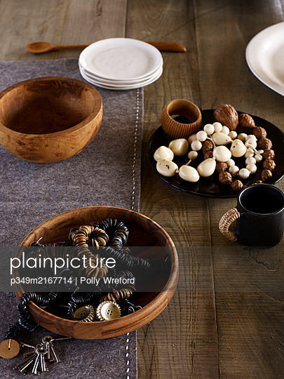 Buttons and beads in wooden bowls and plates with grey felt - p349m2167714 by Polly Wreford