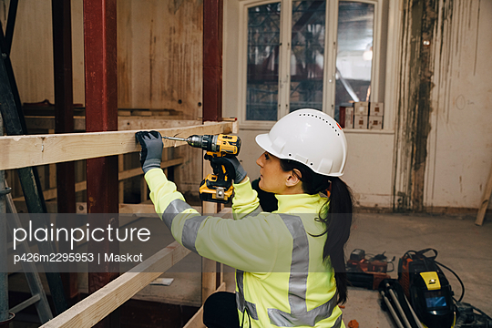 Female worker in hardhat using drill on wooden plank while working at construction site - p426m2295953 by Maskot