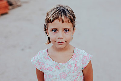Portrait of a 5-year-old girl in a dress facing the camera - p1166m2153808 by Cavan Images