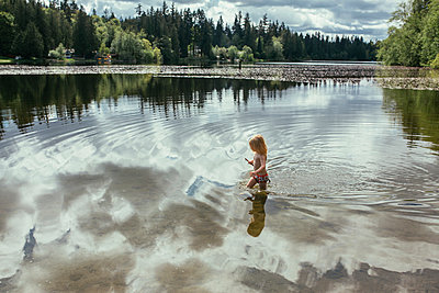 Little Girl Wading through Forest Lake With Reflection of Sky and Trees - p1238m1042086 by Amanda Voelker