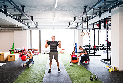 Group of fit seniors with personal trainer in gym - p300m1417064 by HalfPoint