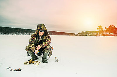Man ice fishing in frozen lake - p555m1311899 by Aleksander Rubtsov