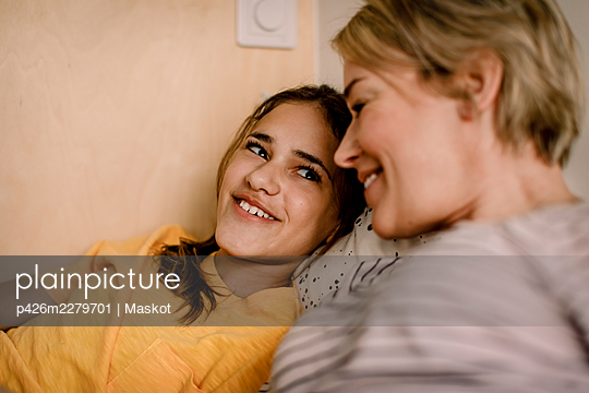 Smiling girl looking at mother in bedroom - p426m2279701 by Maskot
