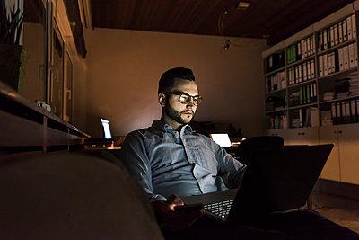 Businessman working on laptop in office at night - p300m1580798 von Uwe Umstätter