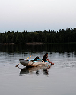 Woman and dog in a rowing boat - p551m2056721 by Kai Peters