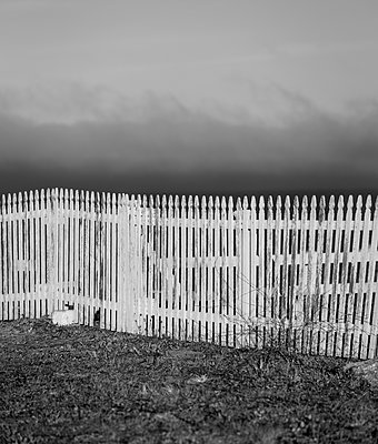 White fence against dramatic sky - p552m2134970 by Leander Hopf