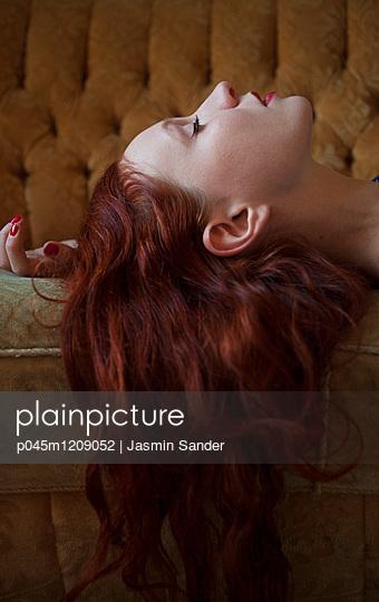 Frau schläft auf Retro-Couch - p045m1209052 von Jasmin Sander