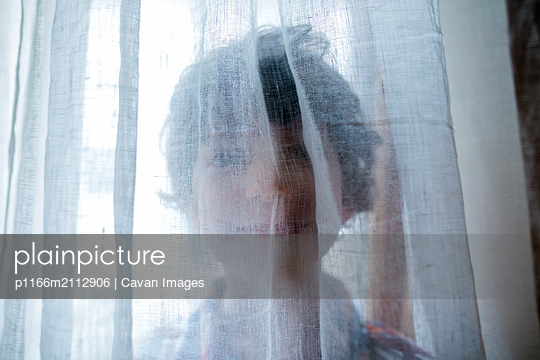 A playful child peers through a gauzy curtain with a big smile - p1166m2112906 by Cavan Images