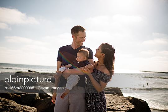 Parents Standing on Jetty Holding Infant Son - p1166m2200995 by Cavan Images