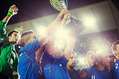 Soccer team celebrating with trophy on field - p1023m923699f by Tom Merton