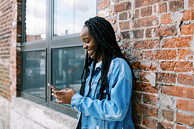 Young black woman scrolling on social media and holding her phone - p1166m2262008 by Cavan Images