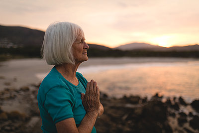 Senior woman meditating at beach during sunset - p1315m1518223 by Wavebreak
