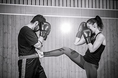 Female kickboxer sparring with coach in sports hall - p300m2144775 von Stefanie Baum