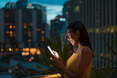 Smiling woman standing on roof terrace at dusk looking at cell phone, Bangkok, Thailand - p300m2156482 by Mauro Grigollo
