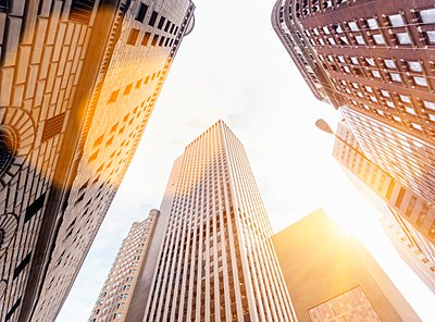 Low angle view of sunlit office skyscrapers, Manhattan financial district, New York, USA - p429m1095436f by Henglein and Steets