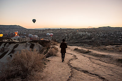 Woman enjoying view and display of hot air balloons in valley, GÌŠreme, Cappadocia, Nevsehir, Turkey - p429m2138456 by Rosanna U