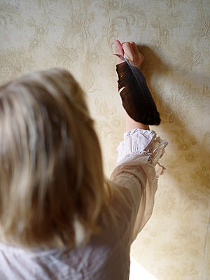 Girl holding quill against wall - p945m1465910 by aurelia frey