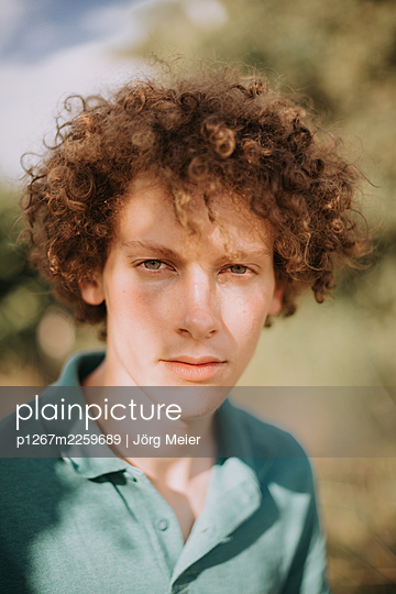 Young man with curly hair, portrait - p1267m2259689 by Jörg Meier