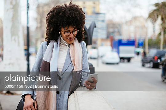 Spain, Barcelona, smiling woman with cell phone and earphones in the city - p300m1567902 by Bonninstudio