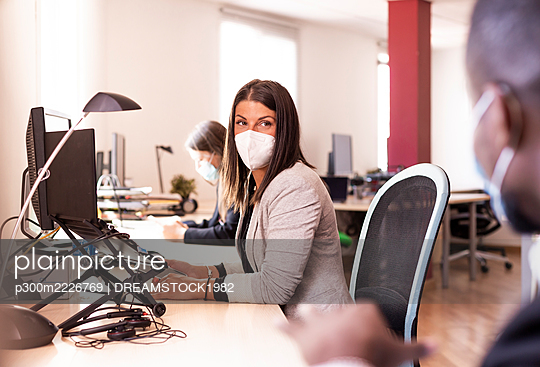Female business in face mask looking at colleague while sitting at desk in office during COVID-19 - p300m2226769 by DREAMSTOCK1982
