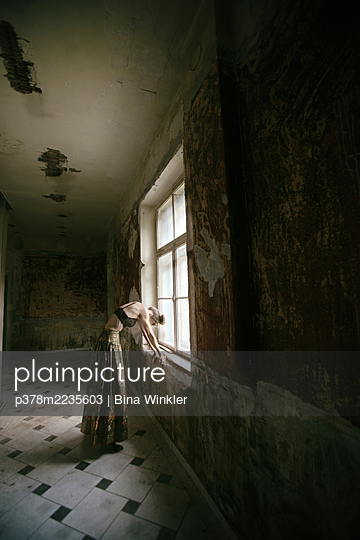 Woman posing in abandoned building - p378m2235603 by Bina Winkler