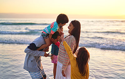 Happy family wading in ocean surf on sunset beach - p1023m2200845 by Trevor Adeline
