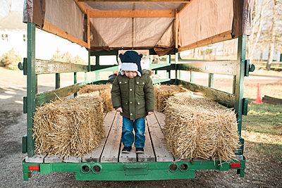 Full length of boy standing on vehicle trailer by hay bales at farm - p1166m1555726 by Cavan Images