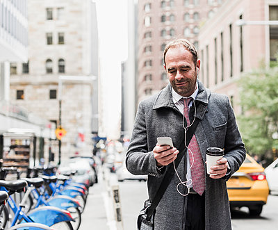 USA, New York City, businessman on the move in Manhattan looking on cell phone - p300m1205757 by Uwe Umstätter