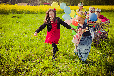 Three children on the move with wooden trolley and balloons - p300m950463f by Jana Mänz