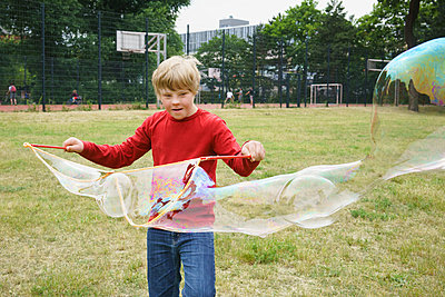 Boy playing with soap bubbles in park - p301m1180568 by Halfdark