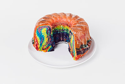 High angle view of rainbow cake in plate on white background - p301m1406356 by Norman Posselt