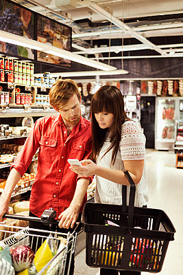 Couple using mobile phone at supermarket - p426m1017980f by Maskot