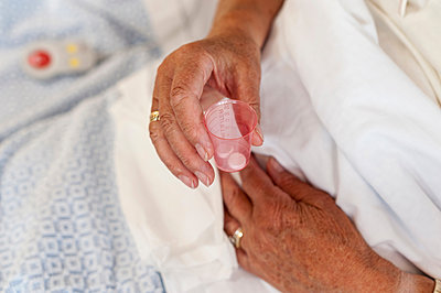 Cropped view of patient's hand holding pills - p429m1197943 by Arno Masse