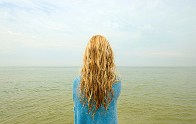 Backview of girl looking out at ocean - p429m839084 by Mischa Keijser
