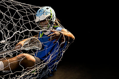 Young male lacrosse player in action falling into net, against black background - p924m2077910 by Edwin Jimenez
