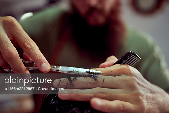 Detailed drawing of a barber cutting hair with scissors - p1166m2212867 by Cavan Images